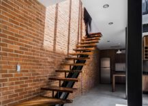Floating-wood-and-steel-staircase-set-against-a-brick-wall-backdrop-217x155