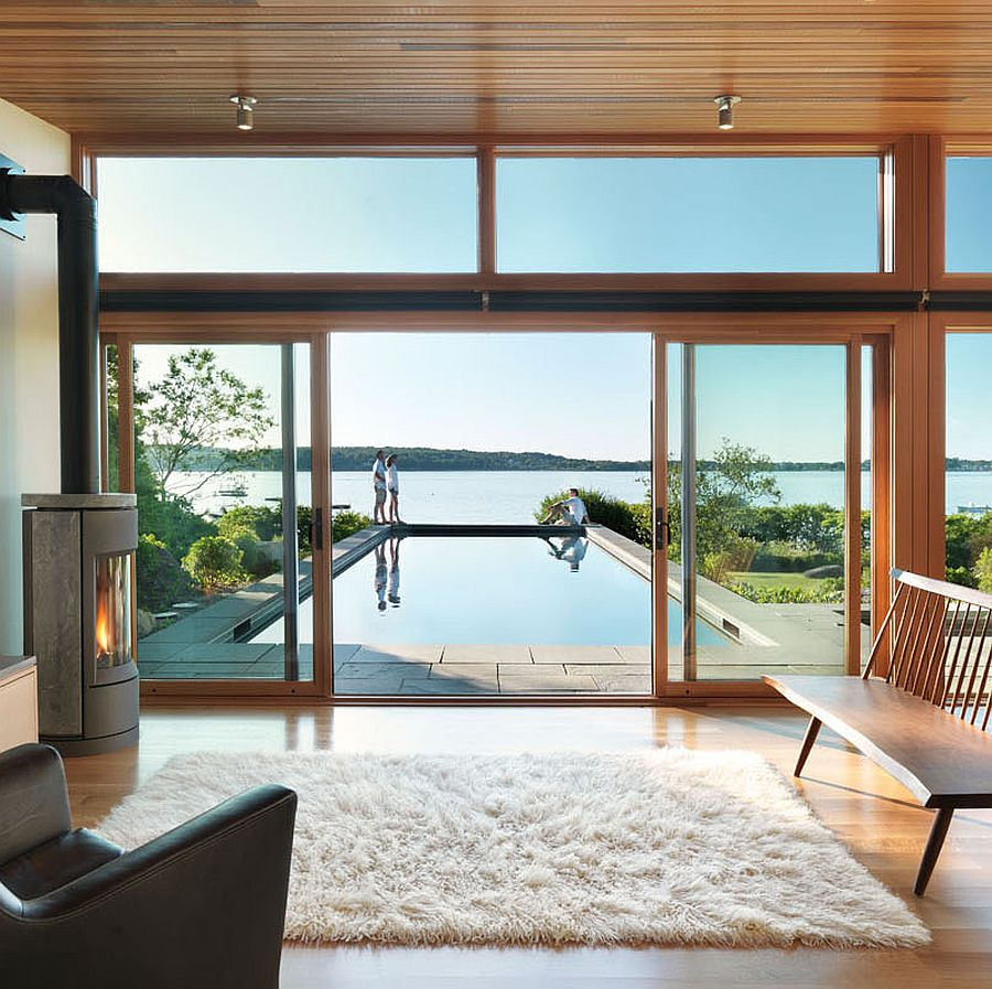 Glass and wood pavilion with lap pool and scenic coastal view beyond
