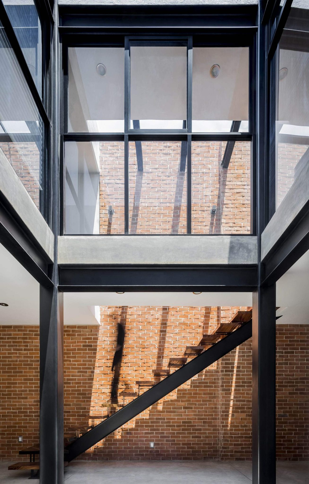 Glass walls and metallic frame give the home an industrial appeal
