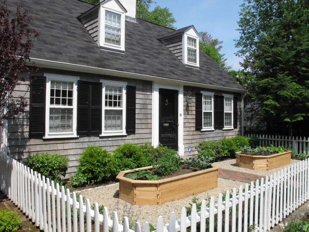 Home-with-a-dark-exterior-and-a-white-picket-fence