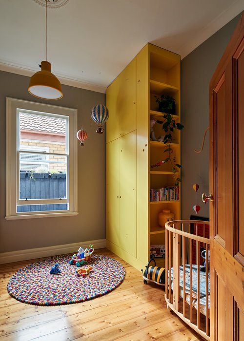 Kids nursery and play area with bright, yellow shelf