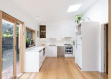 Kitchen in white with skylight 217x155 Cheerful Rear Addition to Melbourne Home in White, Timber and Copper