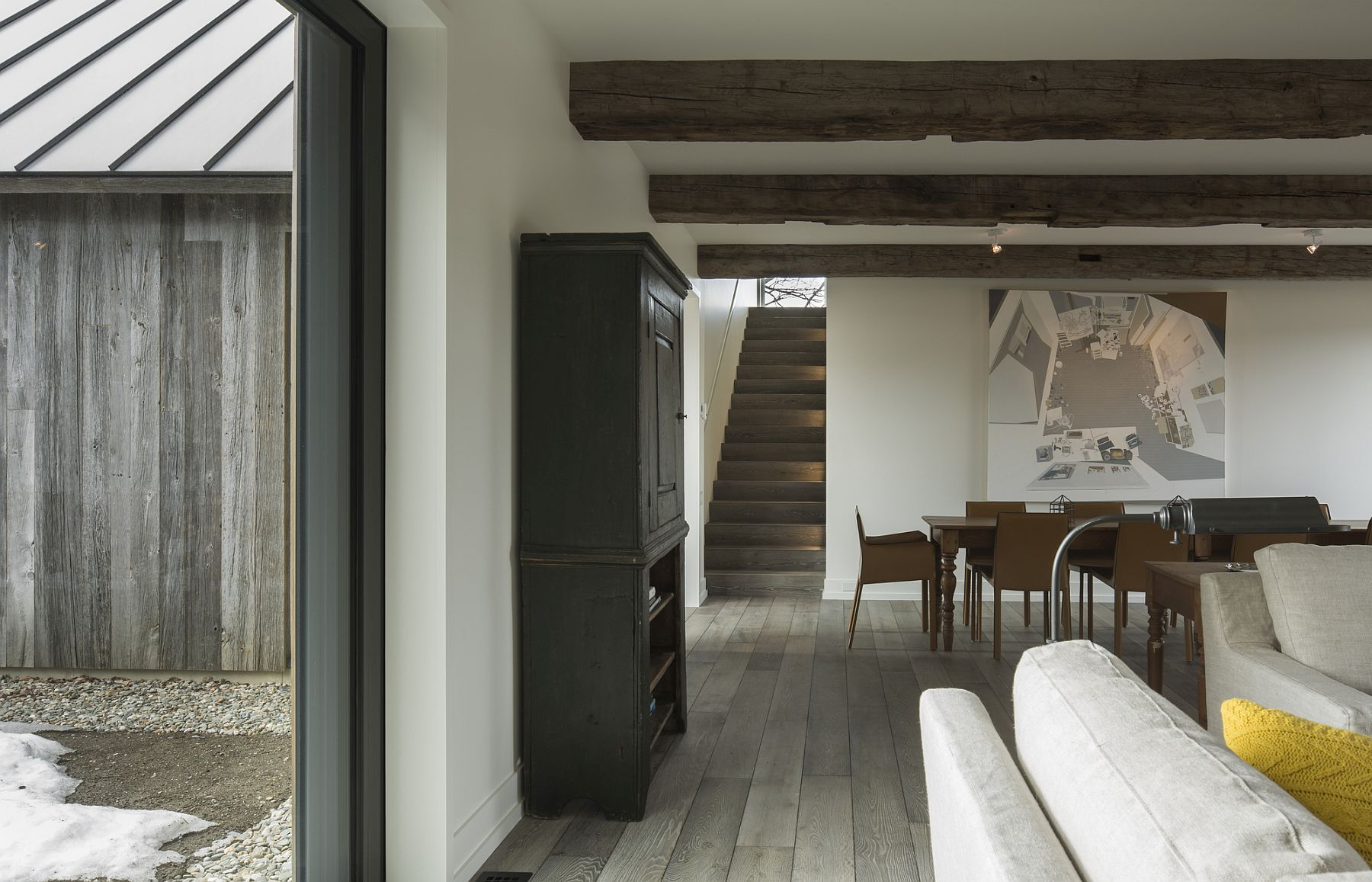 Large-windows-exposed-wooden-beams-and-a-neutral-color-palette-shape-the-living-area