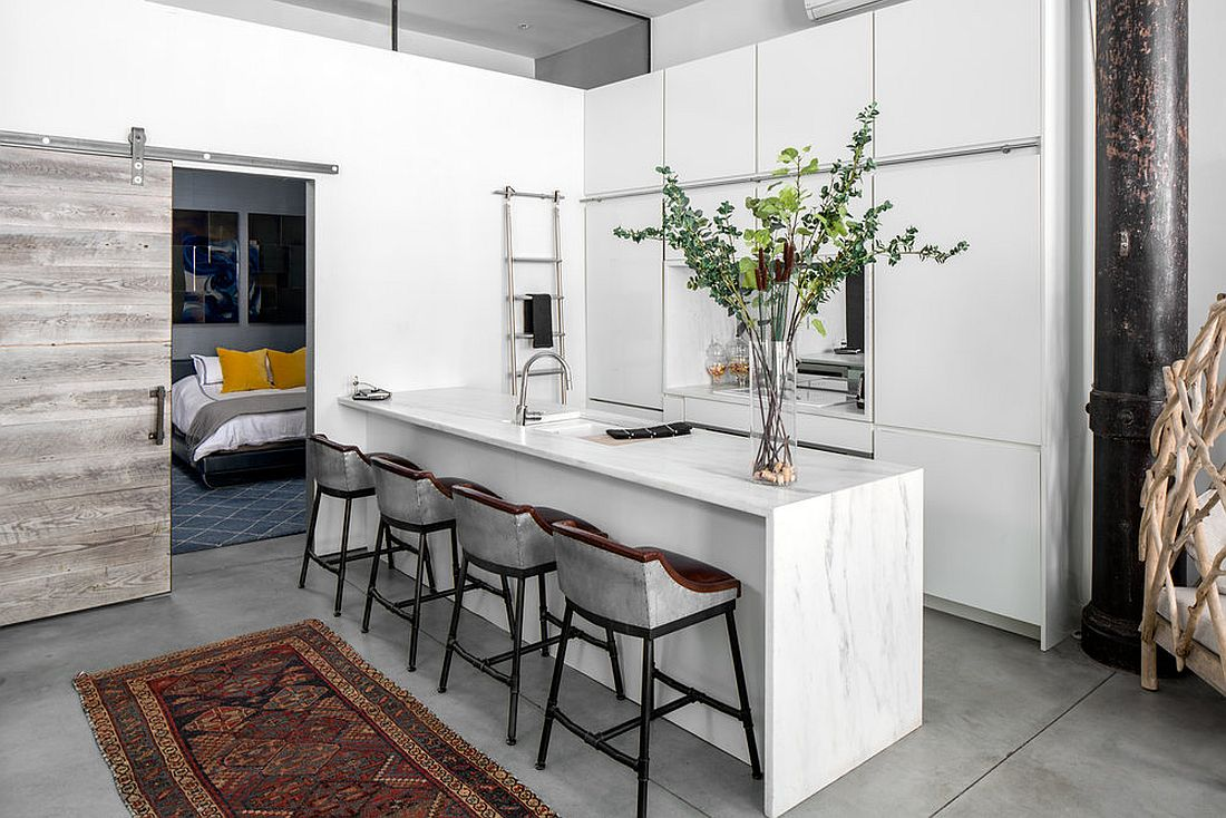 Modern kitchen in white with bedroom next to it and a sliding barn door