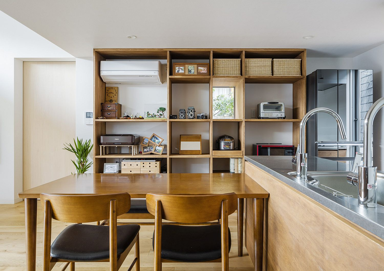 Open shelves in the backdrop of the kitchen and dining area