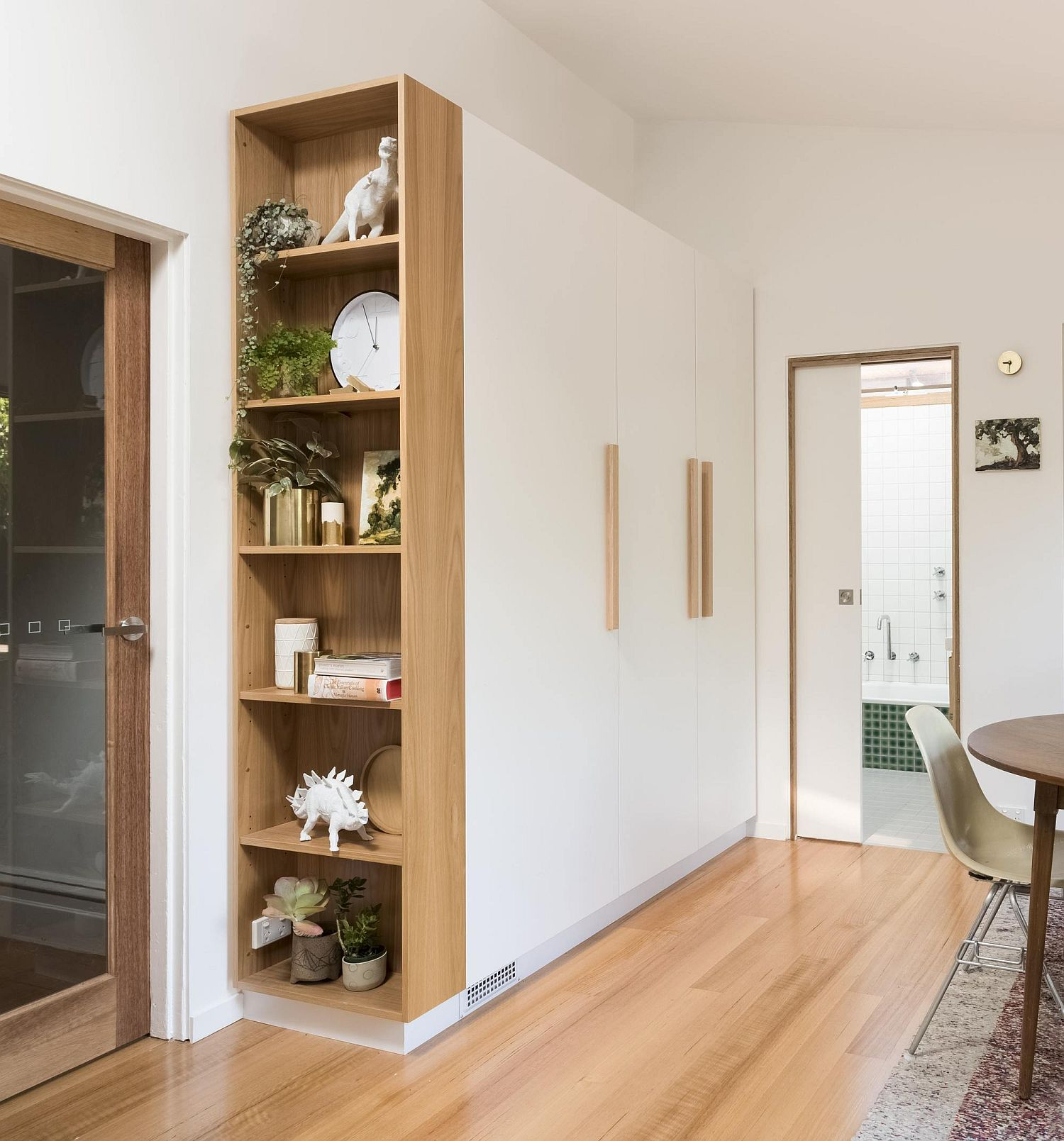 Open wooden shelf next to the large cabinet in white
