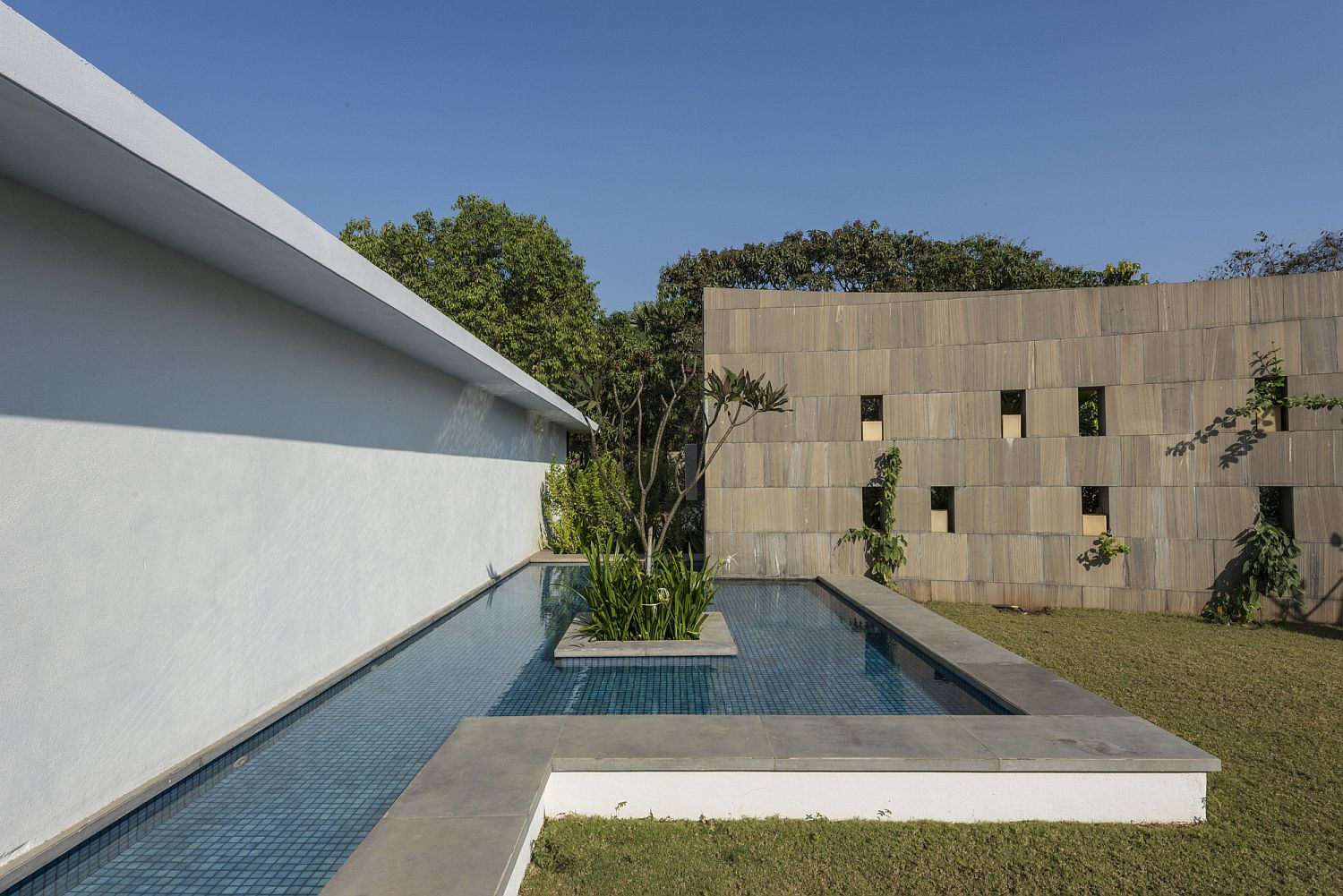 Pool area of the home with curved stone wall