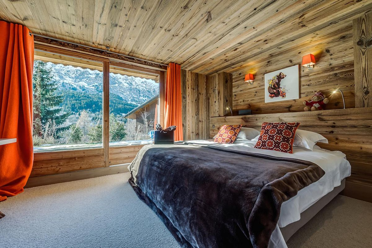 Pops-of-orange-brought-in-by-drapes-and-sconce-lights-into-the-woodsy-bedroom