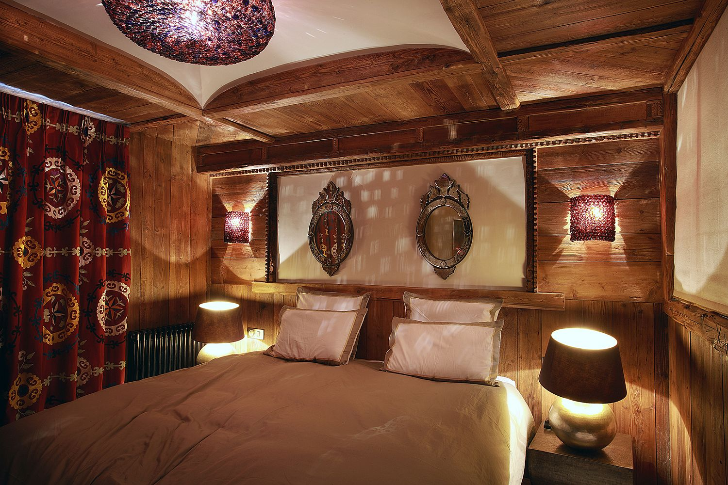 Sconce lighting along with chandelier and bedside lights in the comfy bedroom