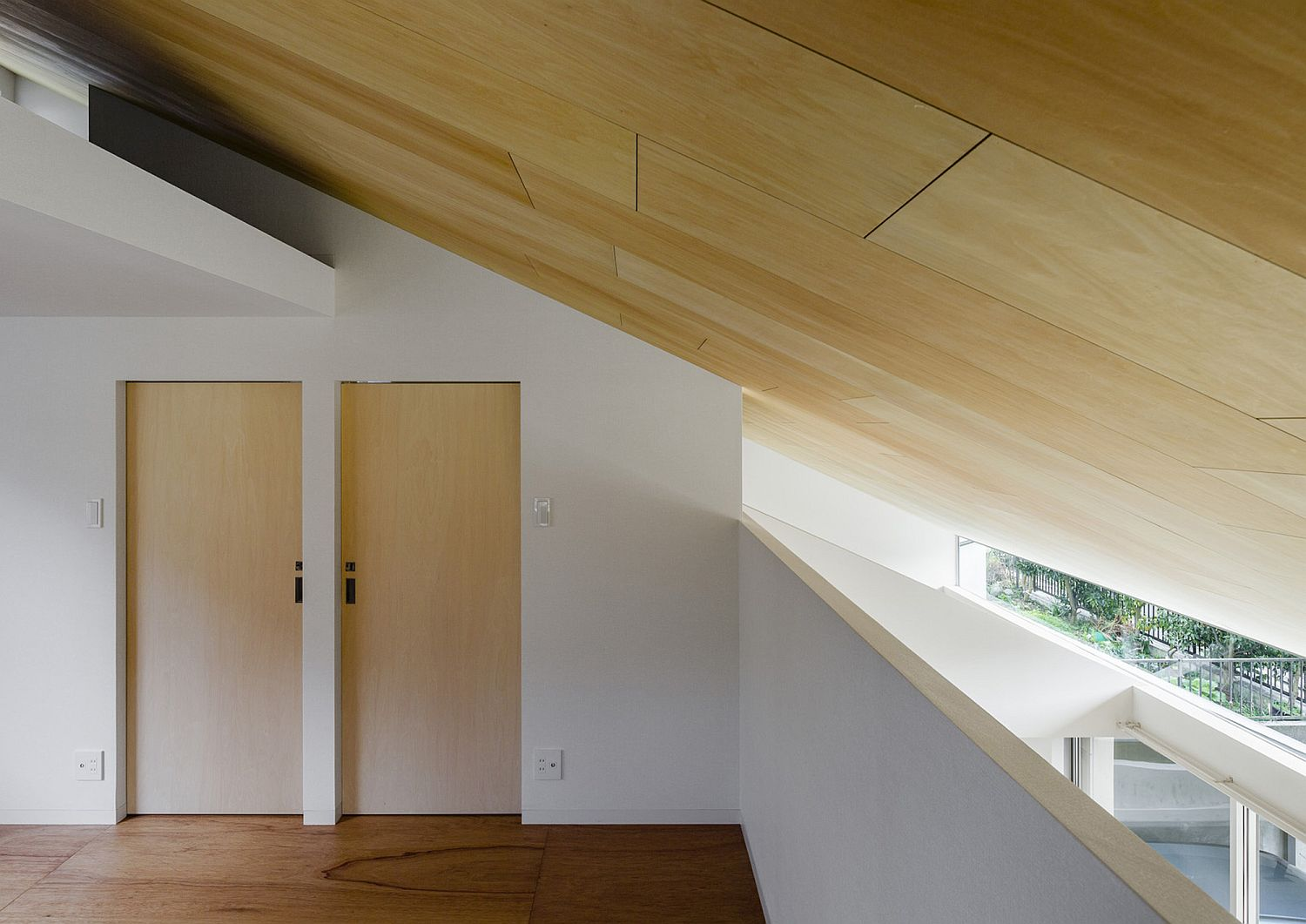 Slanted wooden ceiling of the house adds uniqueness to the home