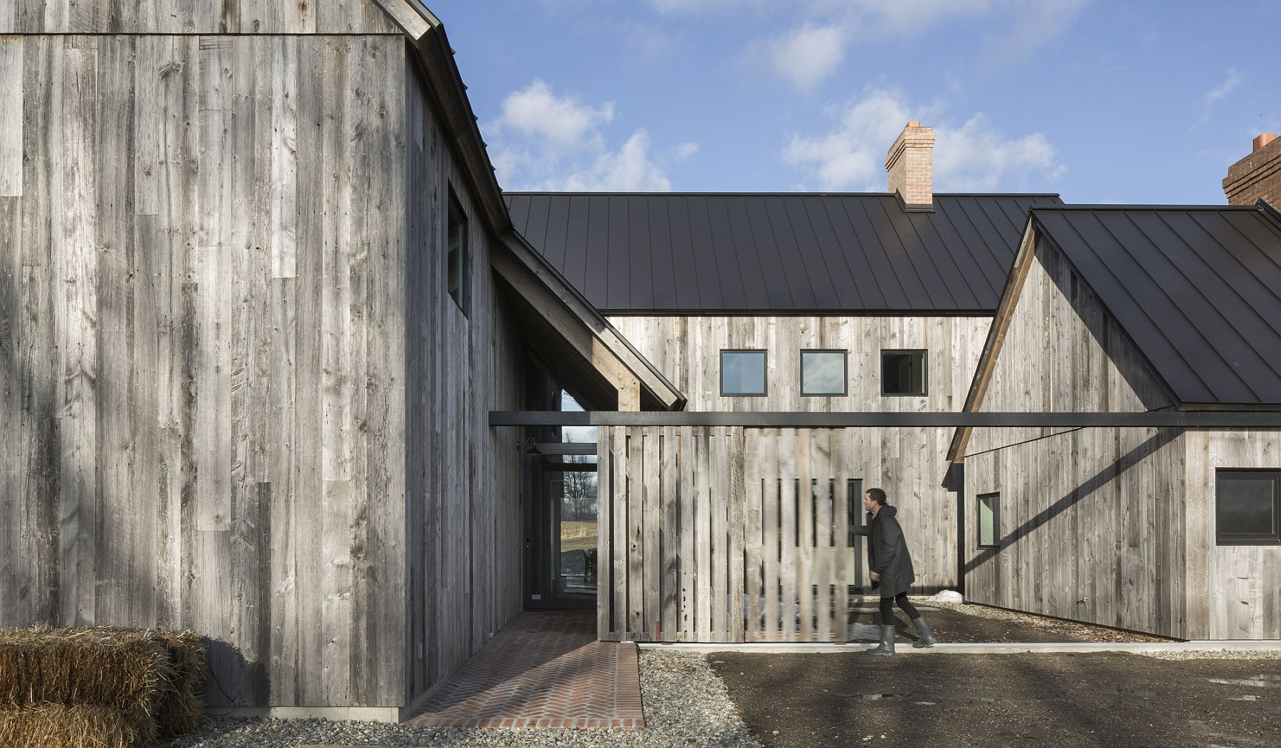 Sliding barn doors and wooden fences provide privacy and protection at the farmhouse