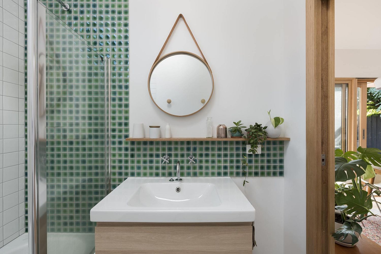 Small green tiles in the bathroom along with a small vanity and stylish mirror