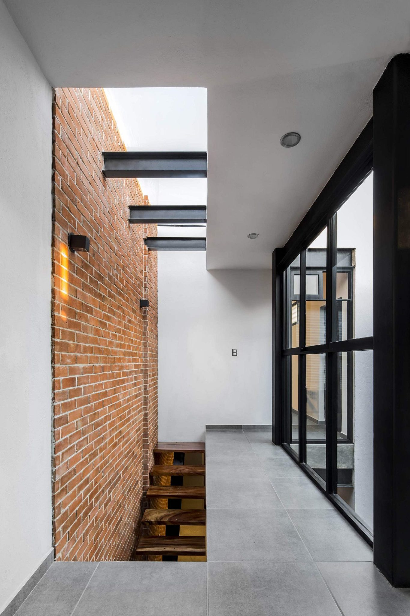 Stairwell and skylight bring natural light into the industrial modern home