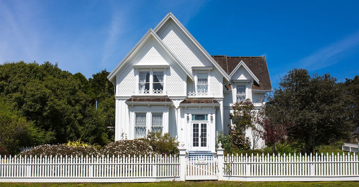 Tall victorian house with a vintage white picket fence