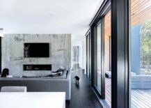 Ultra-minimal-interior-with-concrete-accent-wall-in-the-TV-room-217x155