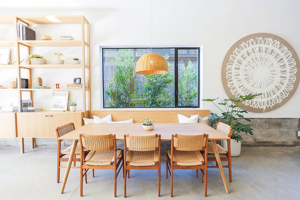 Wooden dining table, chairs and pendant light in natural materials creates a cozy visual