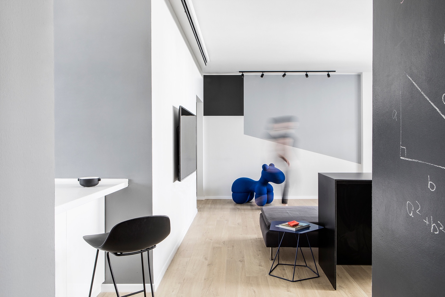 A dark blue side table and large childs toy in the natanya apartments living space