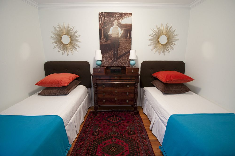 Bedding and carpet bring color to this small guest bedroom in white with twin beds