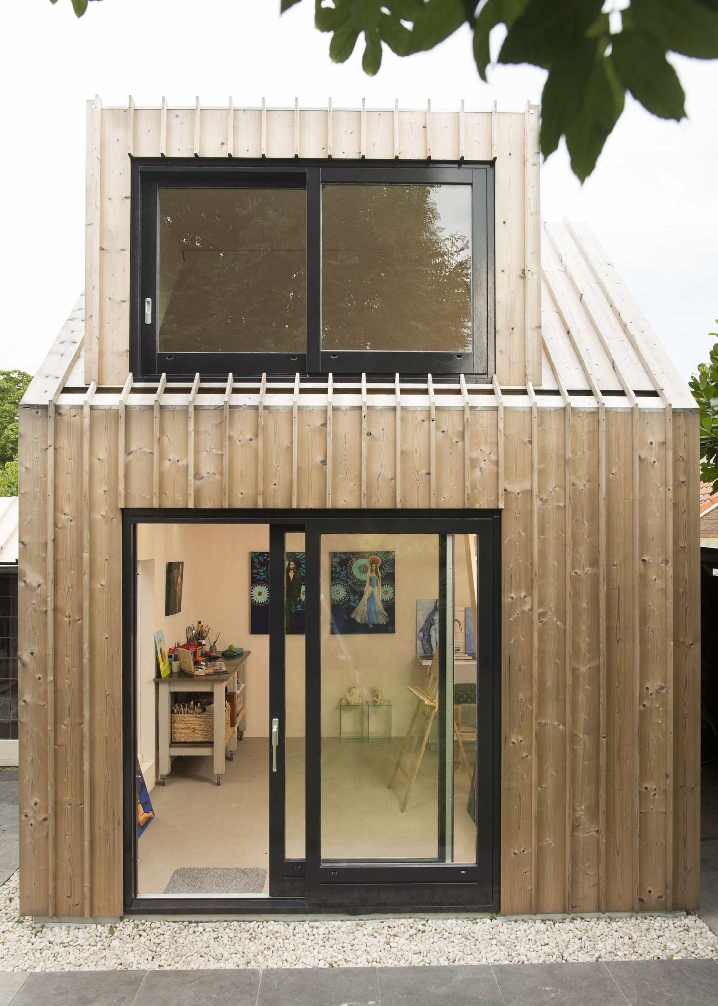 Black-framed doors and windows anchor the light, breezy structure