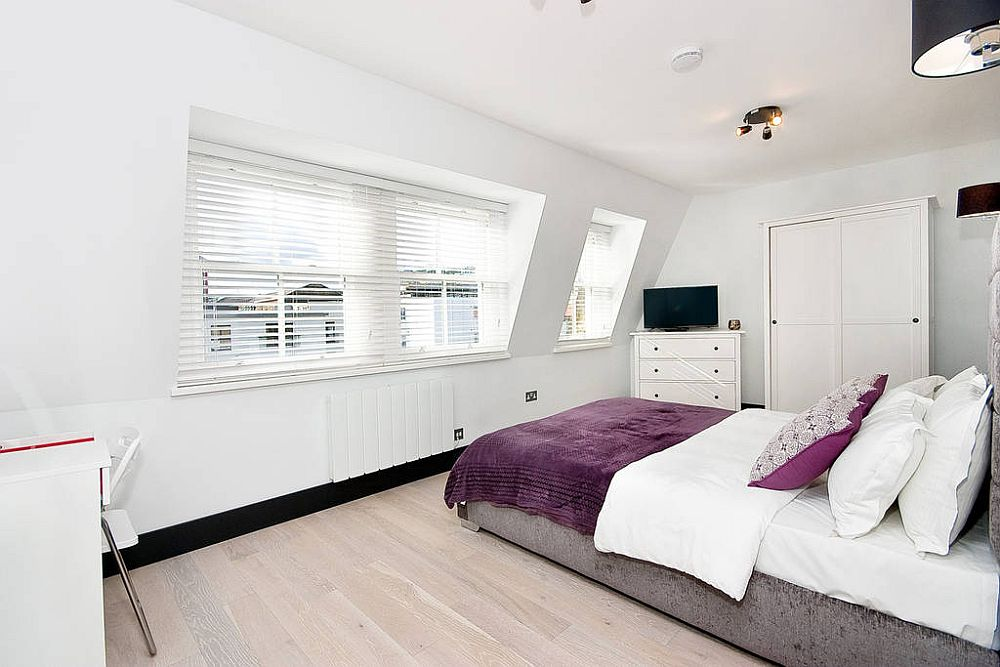 Cheerful and light-filled bedroom in white with purple accents