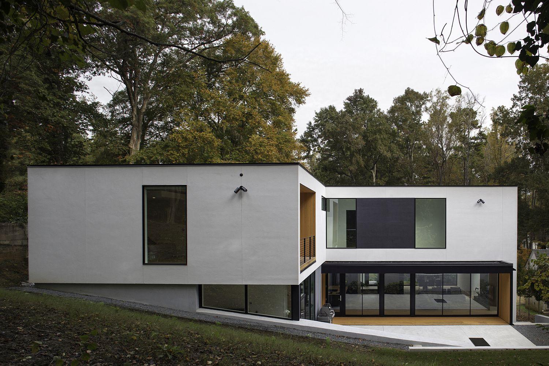 L-förmige moderne Minimal Residence auf einem geneigten Grundstück ...