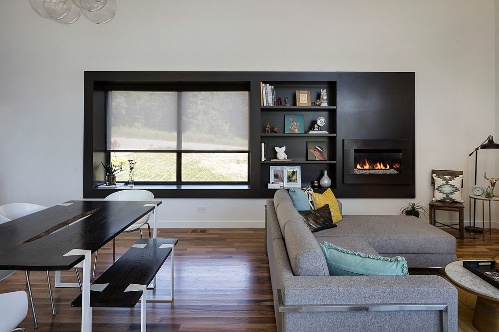 Dark accent wall in the living room with fireplace and a window seat