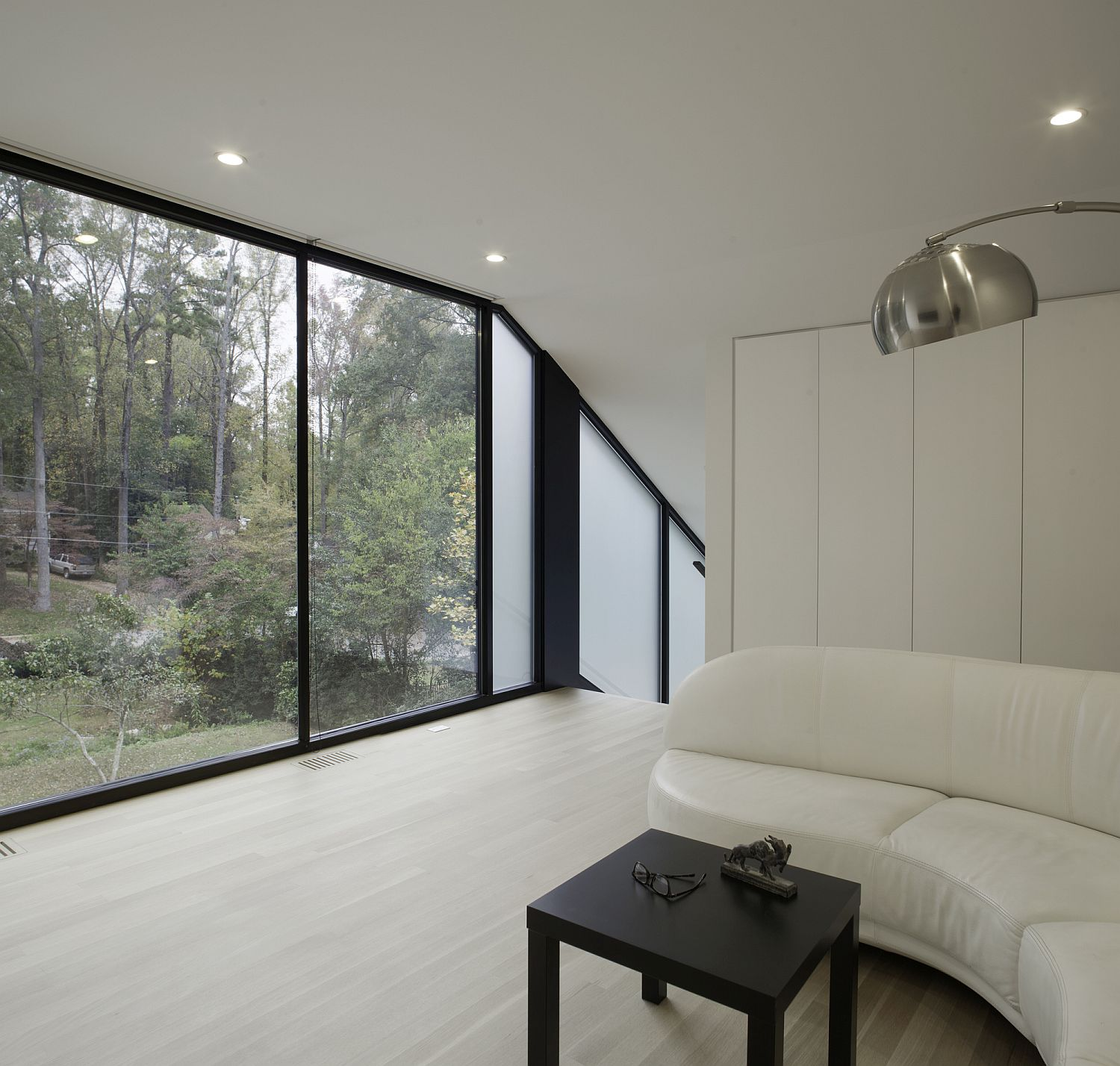 Dark framed windows bring contrast to the contemporary interior in white