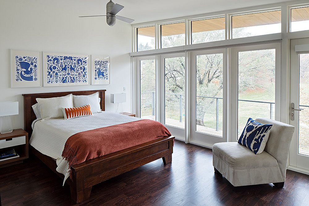 Modern bedroom in white with park views and pops of blue