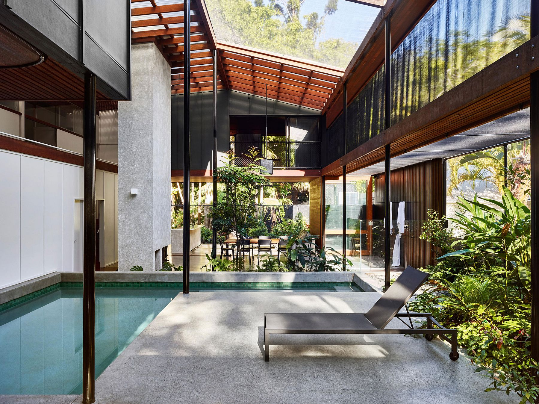 Screened veranda walled by a rainforest serves as a serene Pavilion style house plans