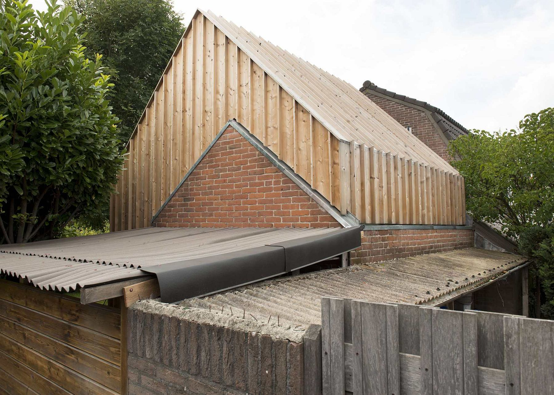 Original brick walls of the old shed are combined with new wooden facade