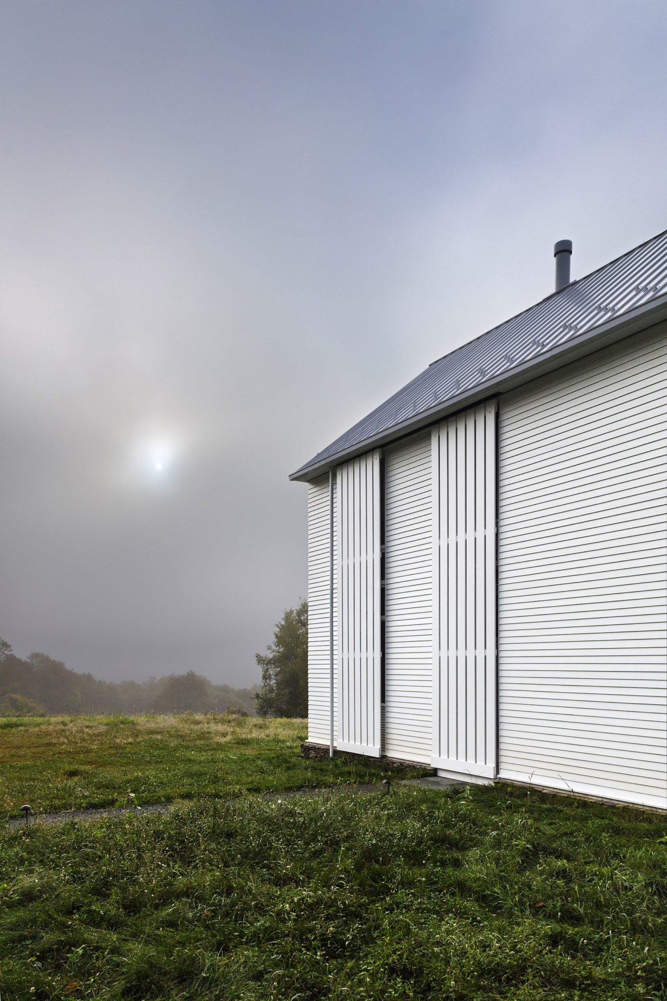 Rolling screens in white shape the exterior of the farmhouse style contemporary home