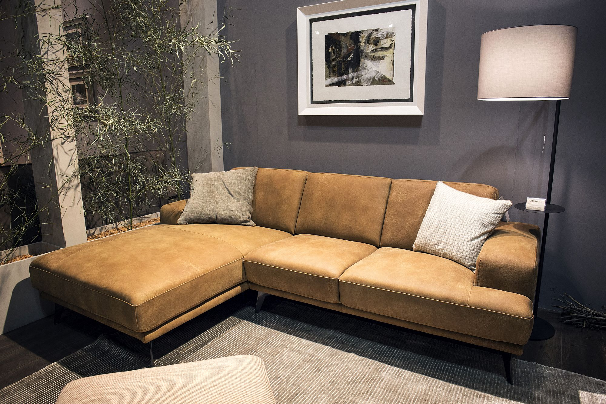 Slim floor lamp in the corner with a large brown sectional next to it