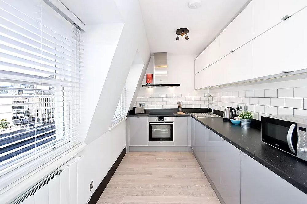 Space-savvy L-shaped kitchen in white with black countertop