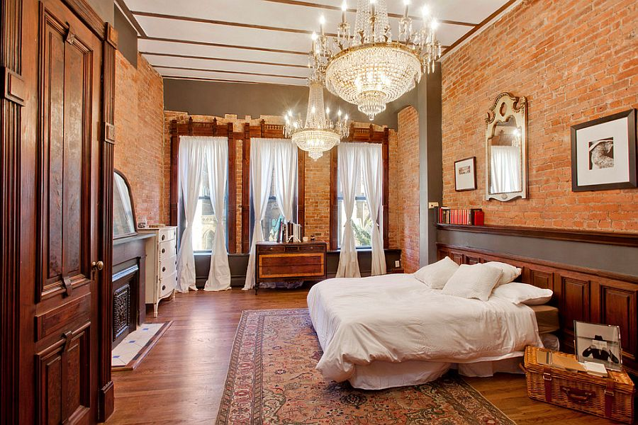 Spacious brick walled bedroom with twin chandeliers