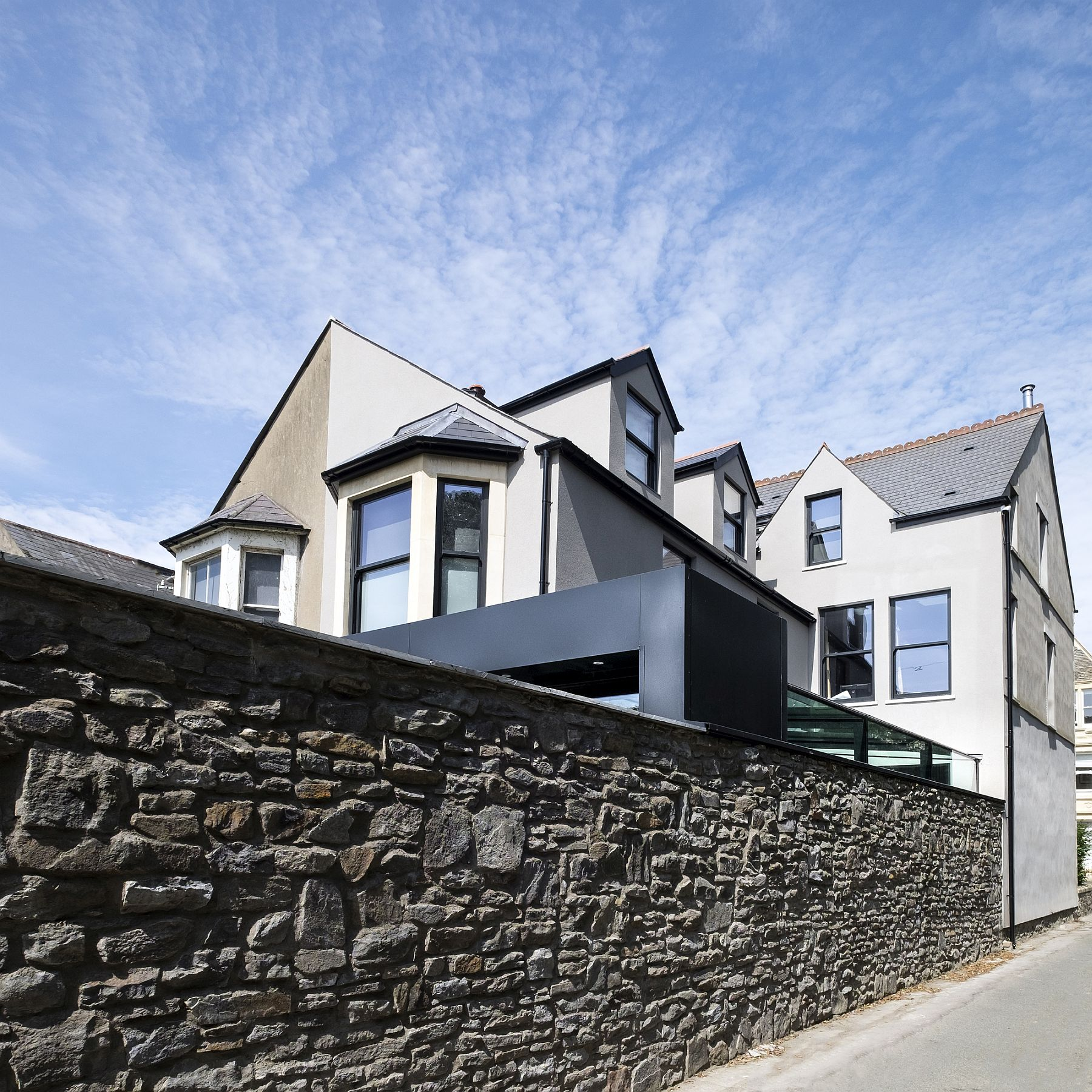 Striking aluminum extension of the Victorian House is partly visible from the street