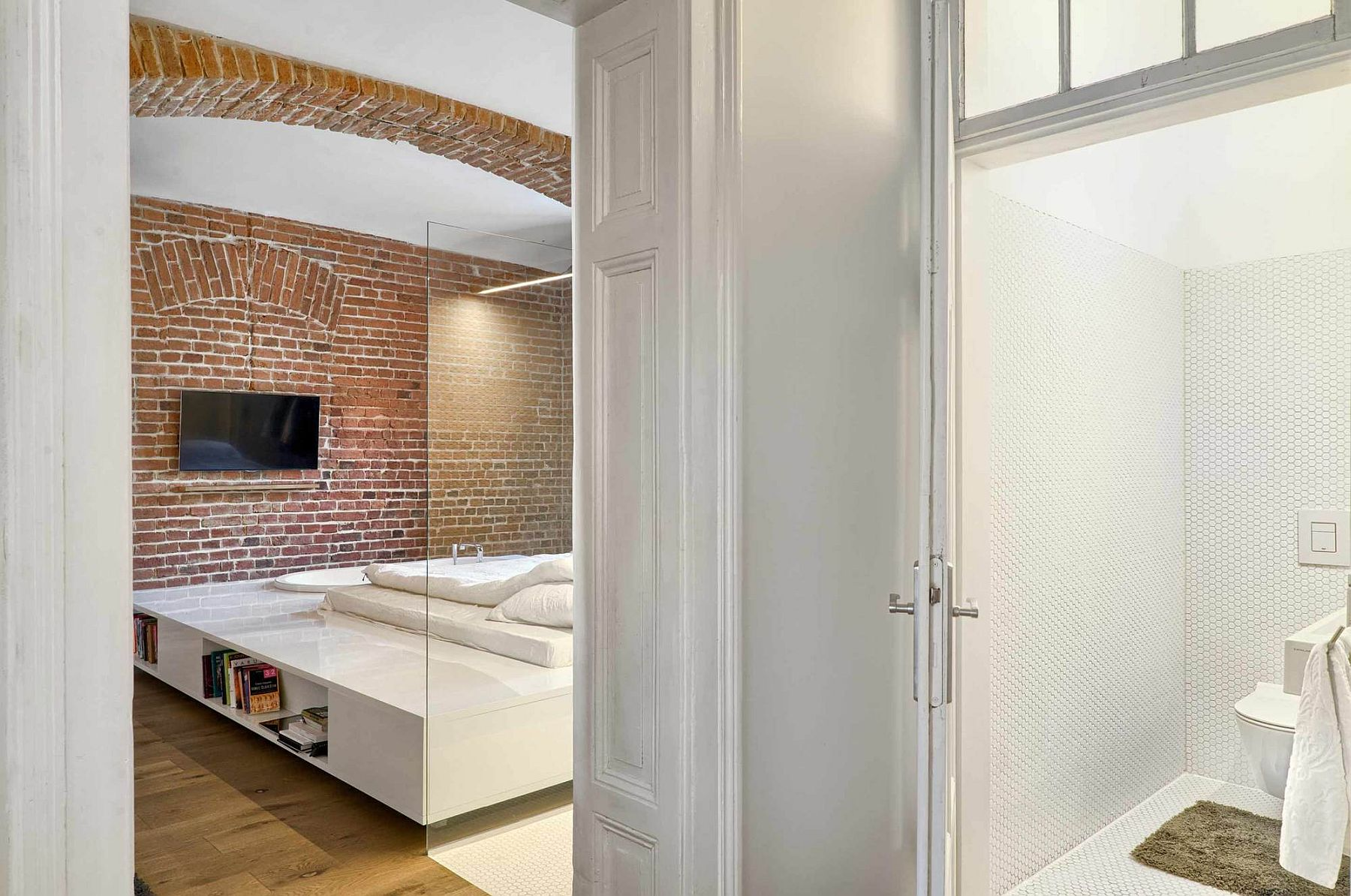 Stunning bedroom in white with brick walls inside the apartment of a football player