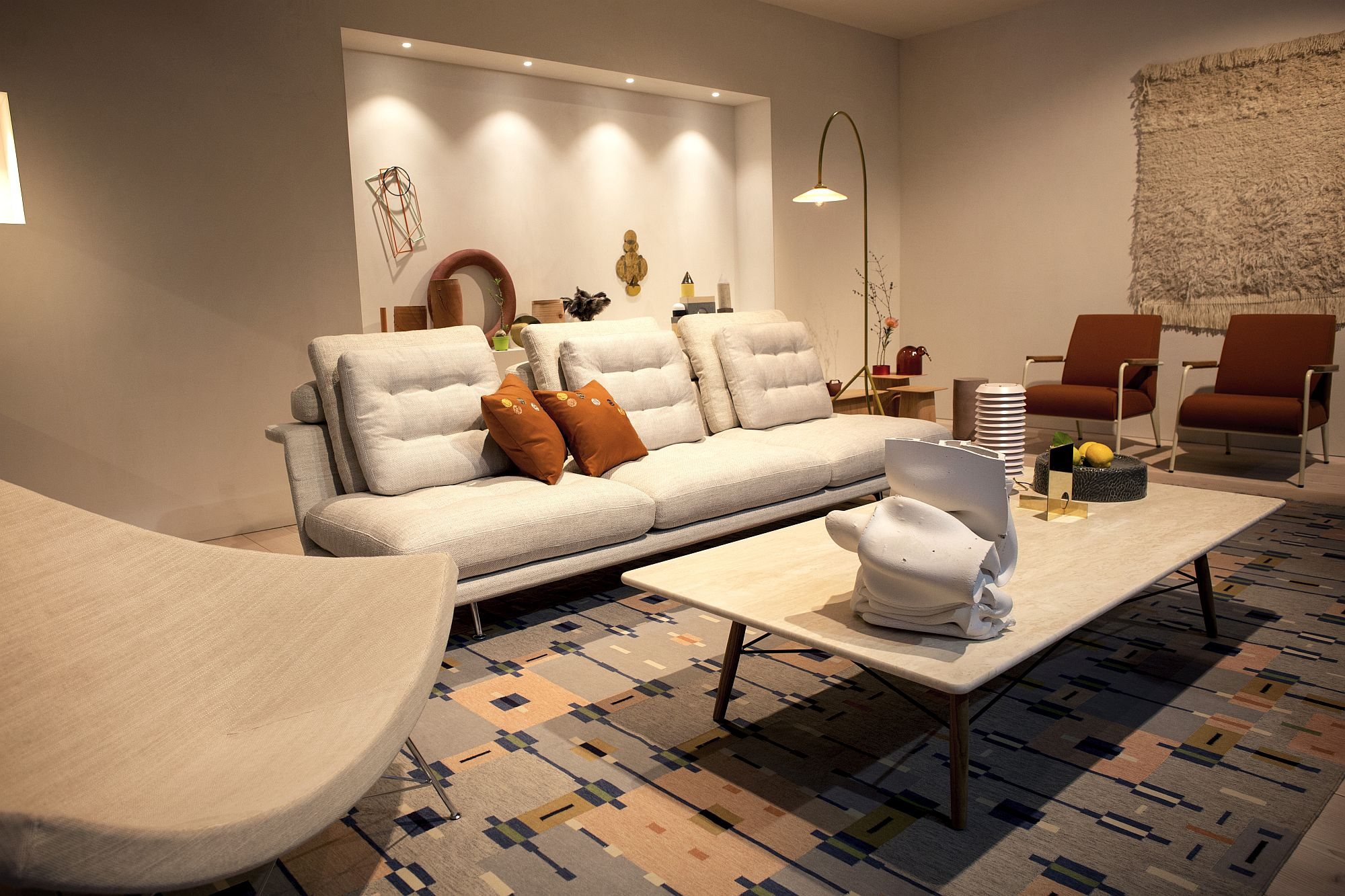 White-living-room-with-pops-of-orange-and-a-sleek-floor-lamp