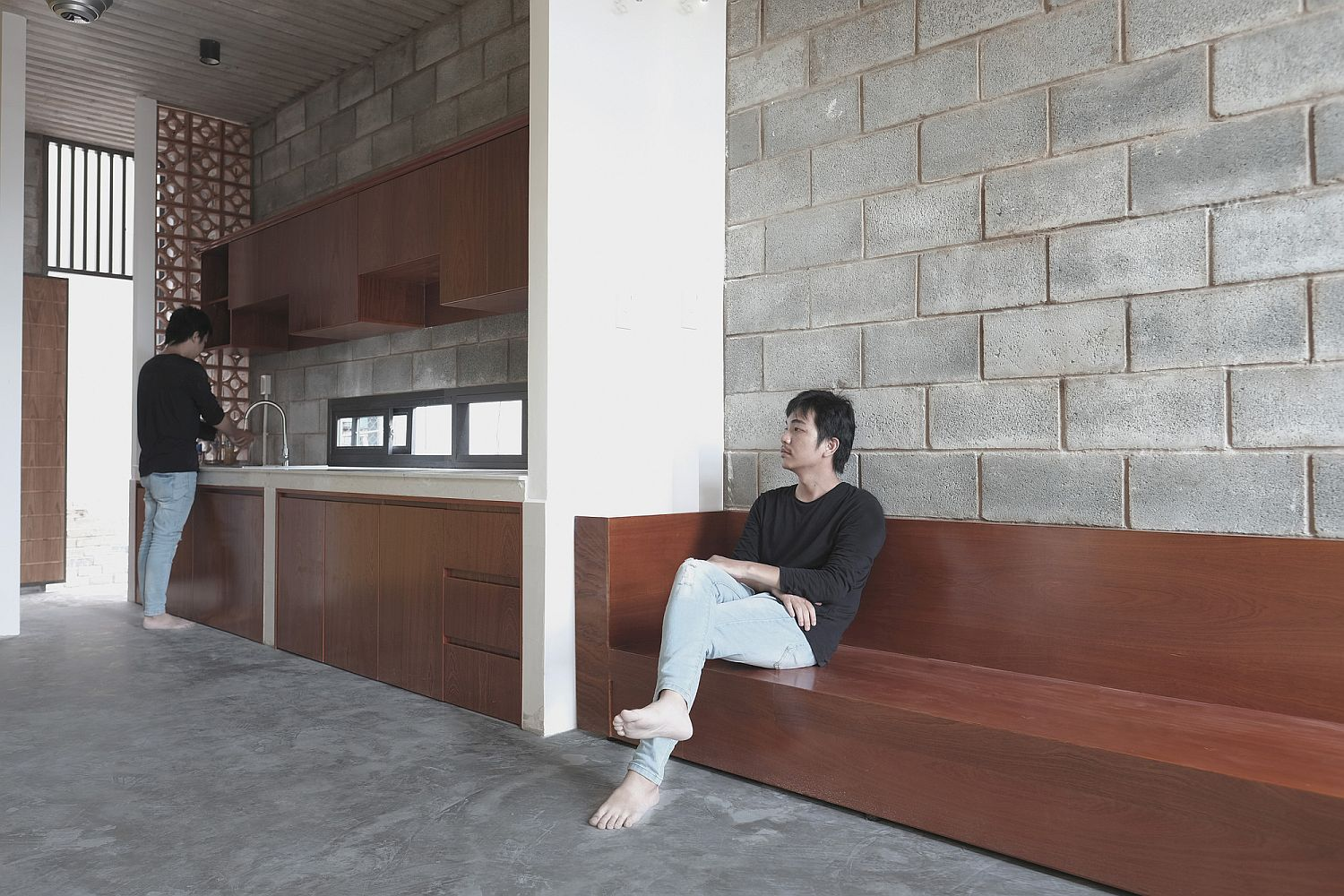 Creative interior with wooden kitchen station and exposed concrete backdrop