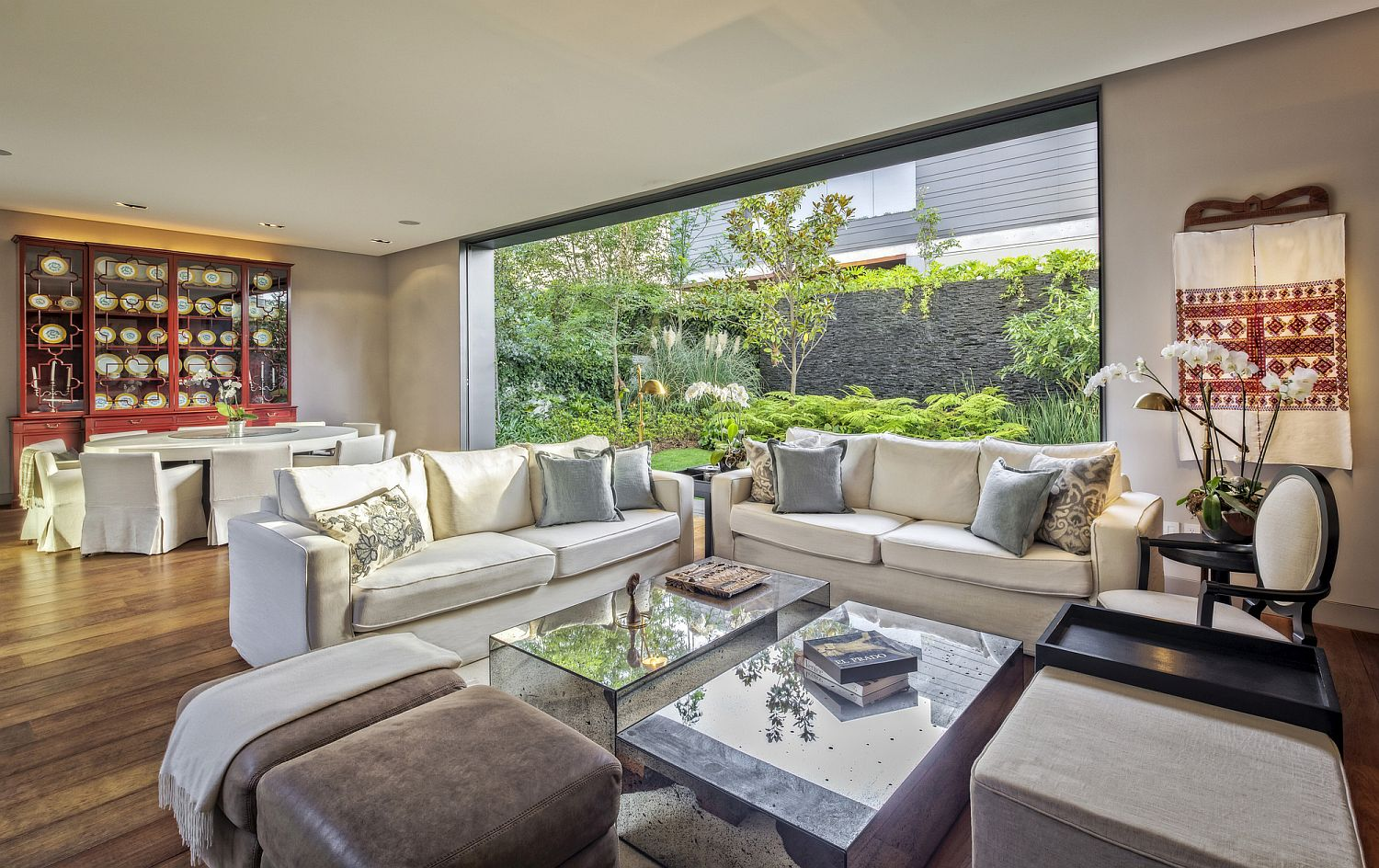 Exquisite living area with dining space next to it and a fabulous garden outside
