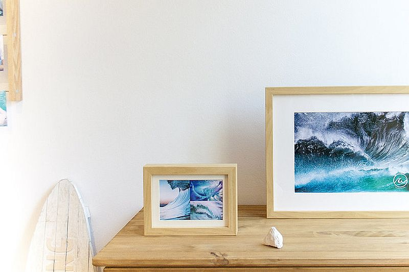 Framed images of sand and surf add to the beach style of the bedroom