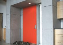 Industrial-style-entry-with-exposed-concrete-duct-pipes-and-a-splash-of-bright-orange-217x155