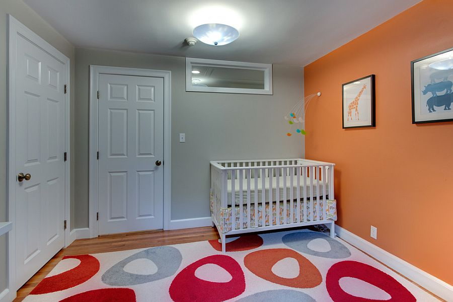 Modern nursery with spunky orange accent wall