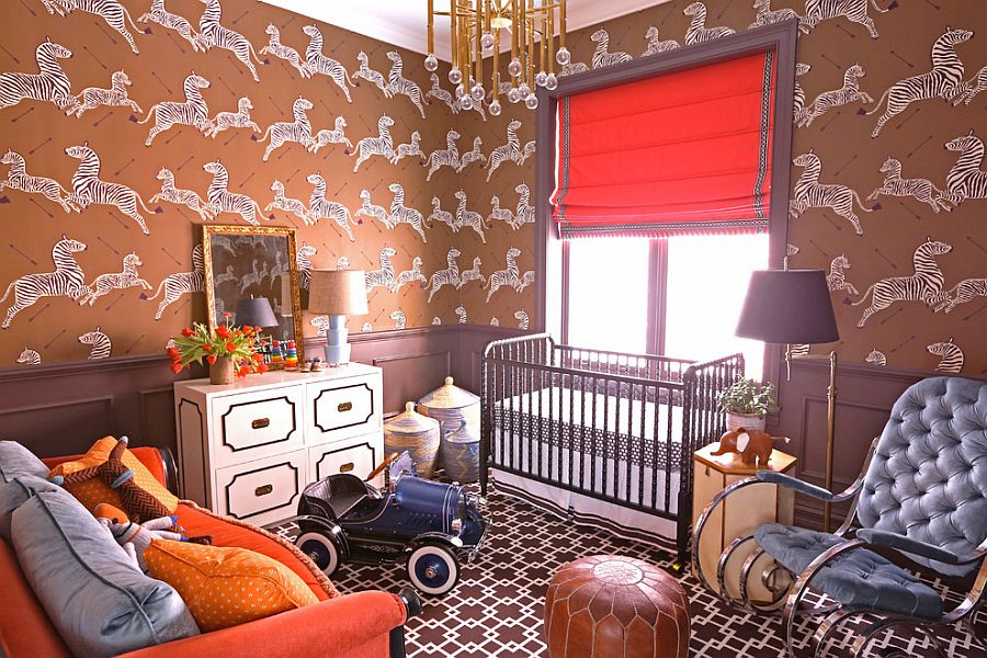 Orangish red wallpaper, bright orange window shade and couch create a beautifully eclectic nursery