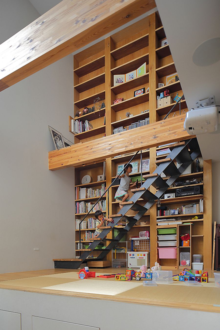 Slim staircase in front of the bookshelf connects the various levels