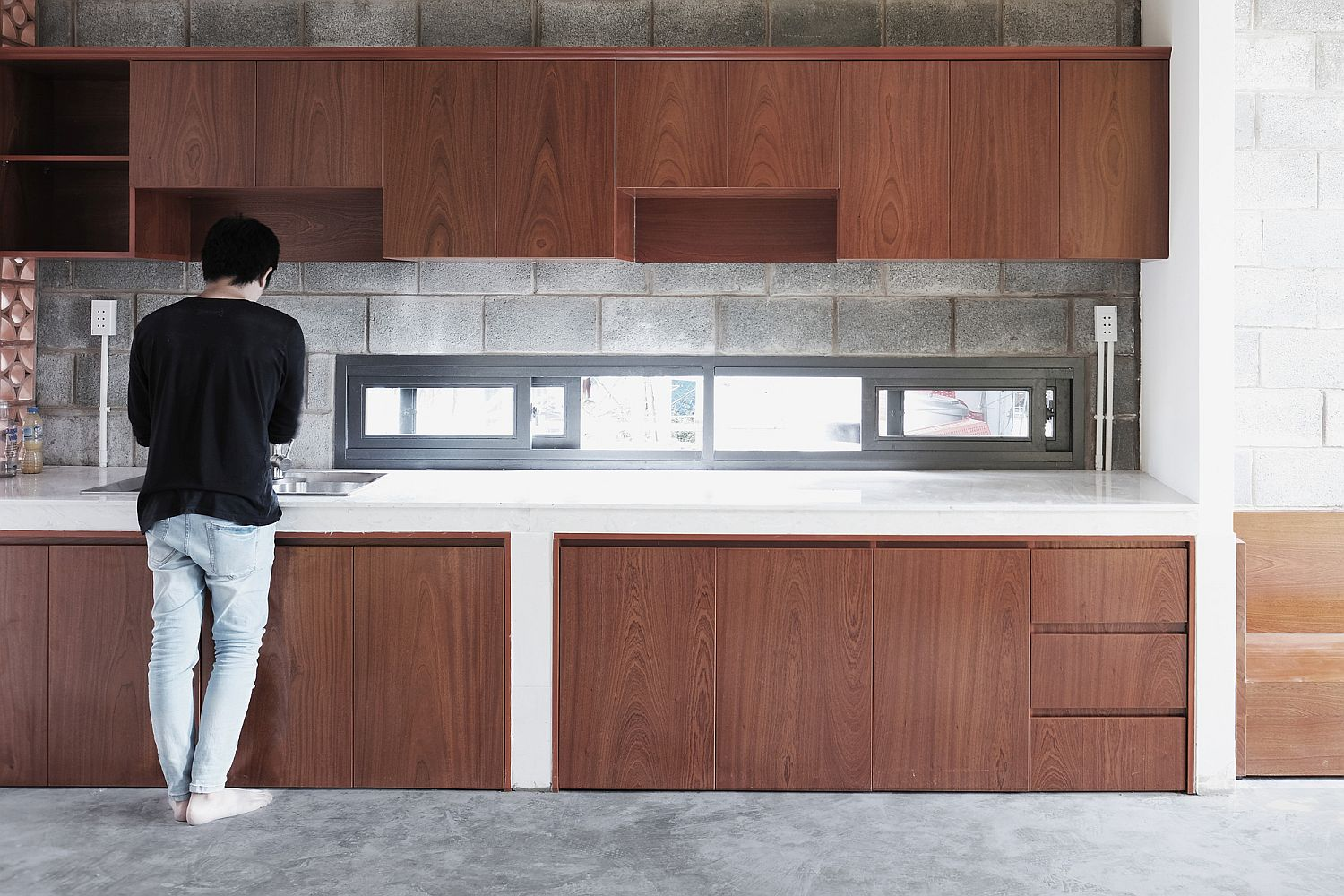 Small and narrow window above the kitchen station brings in natural light