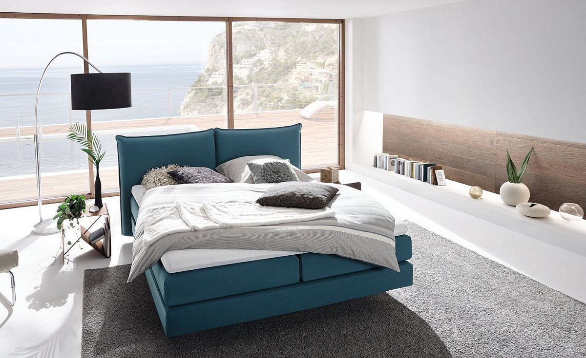 Stylish bedroom with lovely floor lamp, blue bed and smart shelving