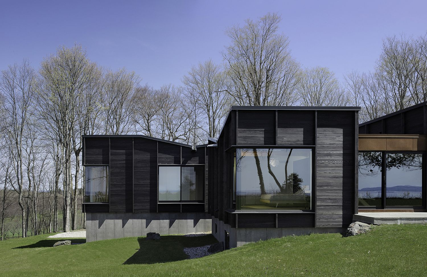 Unique charred wood and glass exterior of the lakeside house