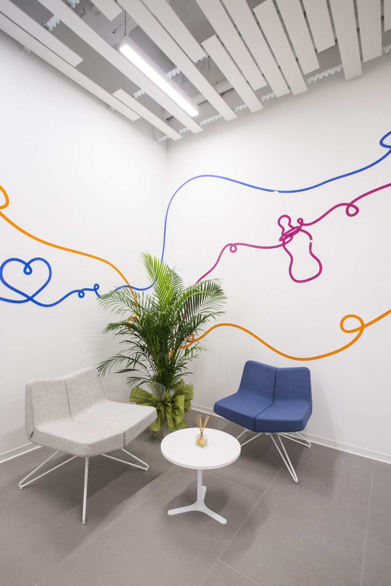 Waiting room in white of the office with a touch of color and whimsical pattern
