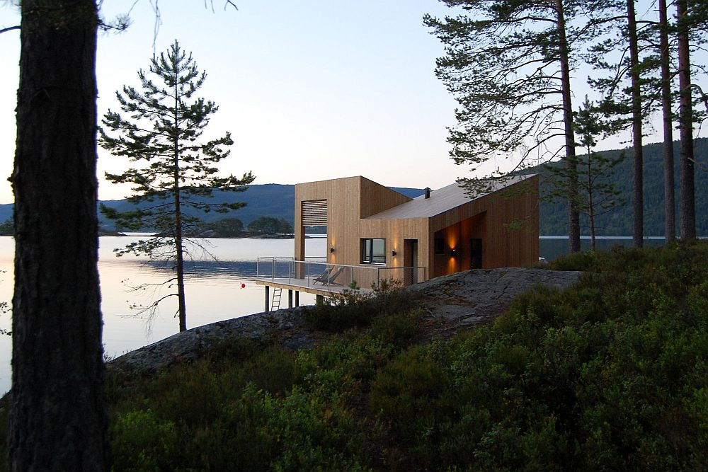 Cabin on stilts on water's edge in Norway