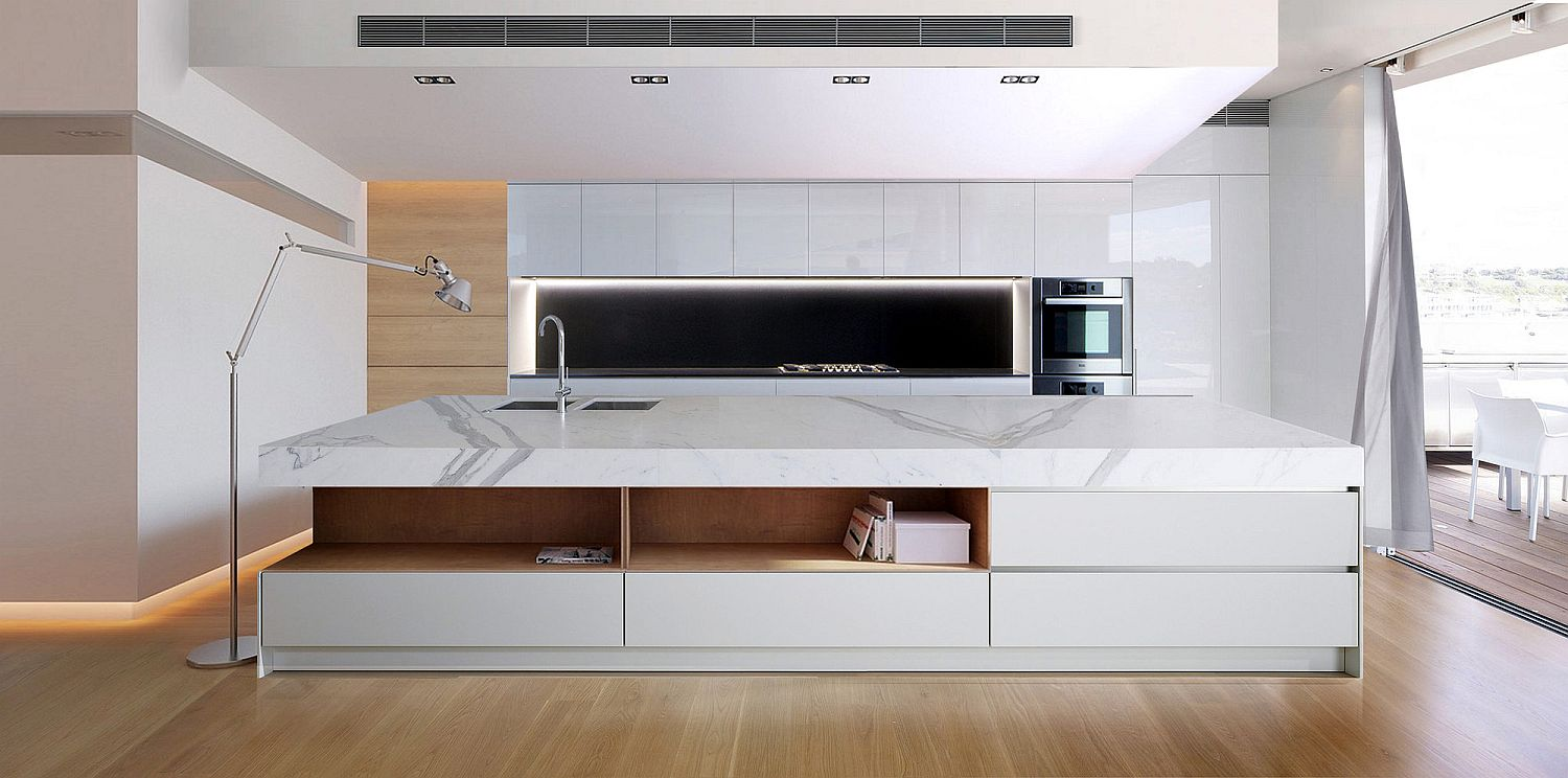 Contemporary kitchen in white with polished central island with marble countertop